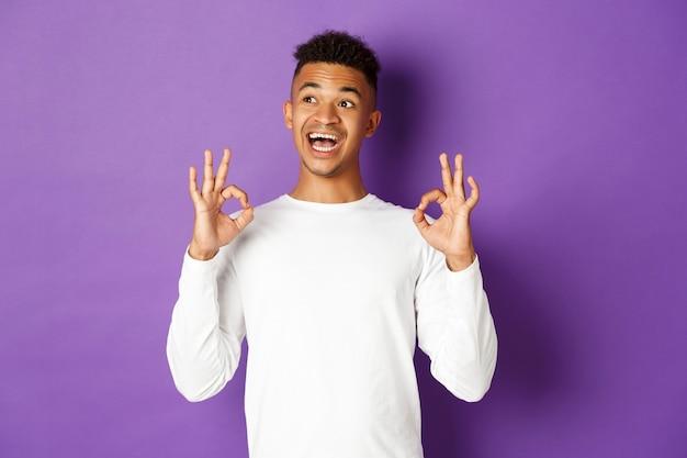 Afbeelding van tevreden mannelijke student, die tevreden kijkt, naar de linkerbovenhoek kijkt en ok teken toont, die zich over paars bevindt.