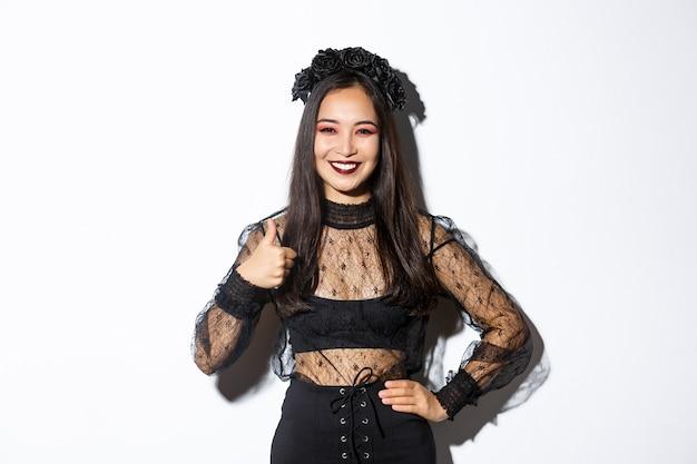 Afbeelding van tevreden vrij aziatisch meisje in halloween kostuum met thumbs-up in goedkeuring, glimlachend tevreden. vrouw in boze heks feestjurk op zoek gelukkig, als iets, witte achtergrond.