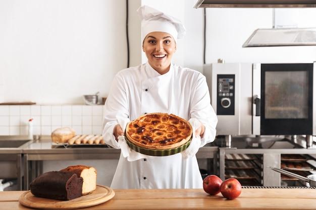 Afbeelding van tevreden vrouw chef-kok dragen witte uniform, poseren in de keuken in het café met gebakken goederen