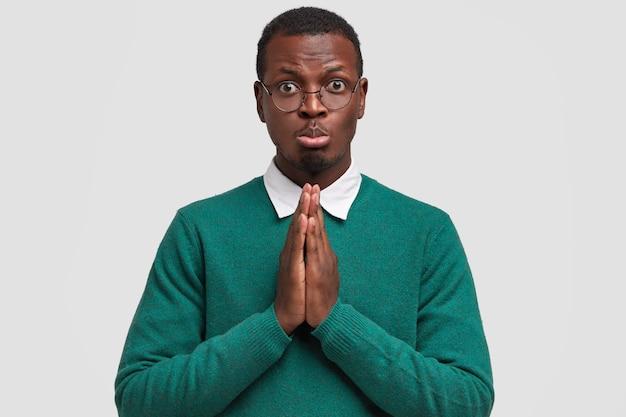 Afbeelding van trieste sombere afro-amerikaanse man houdt de handpalmen tegen elkaar gedrukt, vraagt om hulp in goede vriend, portemonnees onderlip, heeft een donkere gezonde huid