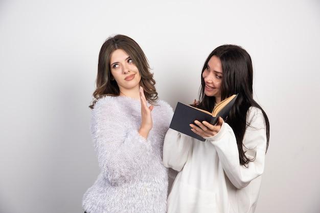 Afbeelding van twee beste vrienden die samen staan en poseren met een boek op een witte muur.