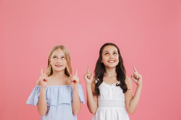 Afbeelding van twee blanke meisjes van 8-10 jaar oud die jurken dragen die naar boven kijken met een glimlach en wijzende vingers op copyspace.