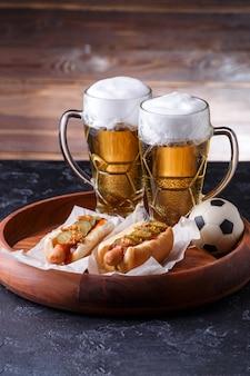 Afbeelding van twee glazen bier, hotdogs, voetbal