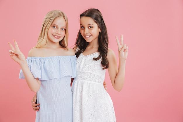 Afbeelding van twee mooie meisjes van 8-10 jaar die jurken dragen glimlachend en overwinningsteken tonen.