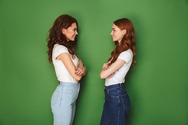 Afbeelding van twee schattige meisjes 20s met rood haar lachend en staan oog in oog met gevouwen armen, geïsoleerd op groene achtergrond