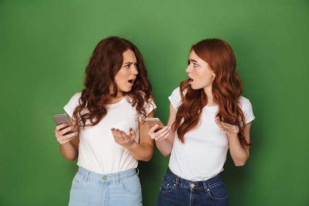Afbeelding van twee verontwaardigde vrouwen met rood haar die mobiele telefoons gebruiken en verontwaardiging uiten, geïsoleerd op groene achtergrond