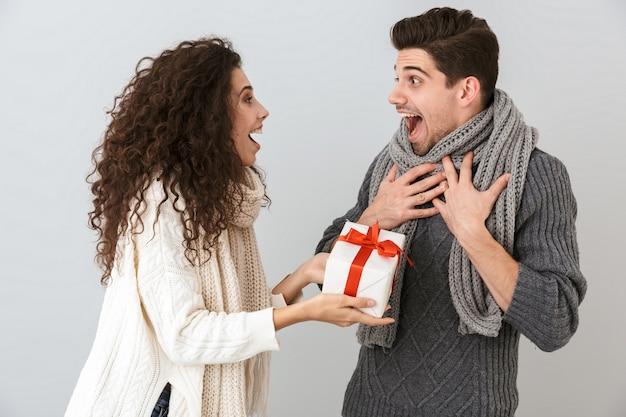 Afbeelding van verbaasde man en vrouw die zich verheugen terwijl ze met de huidige doos staan, geïsoleerd over grijze muur