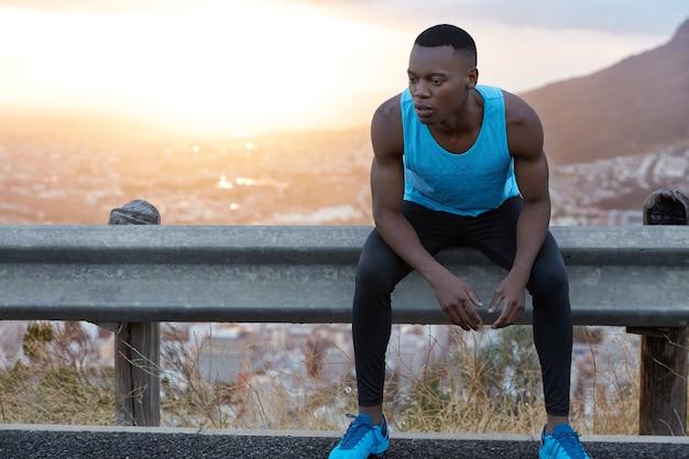 Afbeelding van vermoeide afro-amerikaanse man met doordachte uitdrukking, blijft staren, voelt zich moe na intensieve training, zit bij verkeersbord, prachtige zonsopgang met kopie ruimte voor informatie