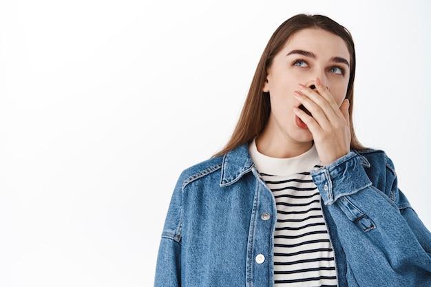 Afbeelding van vermoeide jonge vrouw, verveeld meisje dat gaapt en omhoog kijkt naar promotietekst, zich vermoeid voelt, 's ochtends vroeg wakker wordt zonder koffie, over een witte muur staat