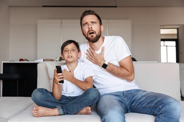 Afbeelding van verontwaardigde emotionele vader met zoon tv kijken, zittend op de bank in de kamer