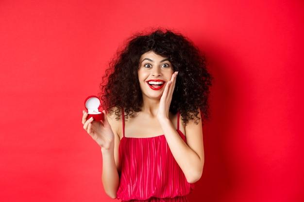 Afbeelding van verrast jonge vrouw met krullend kapsel, rode jurk en lippenstift dragen, verlovingsring tonen, gaan trouwen, staande op studio achtergrond.