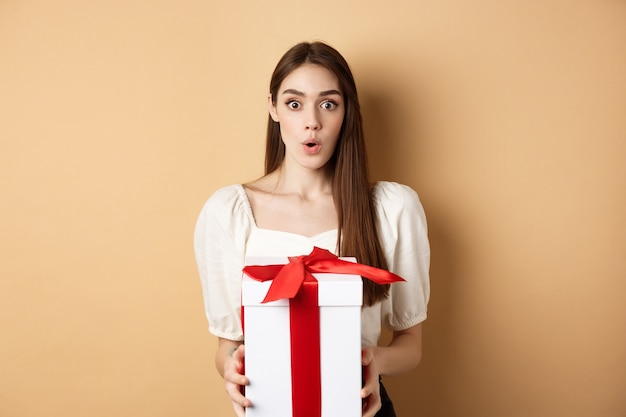 Afbeelding van verrast meisje ontvangt geschenk op valentijnsdag, kijkt met ongeloof en bedrijf aanwezig, staande op beige