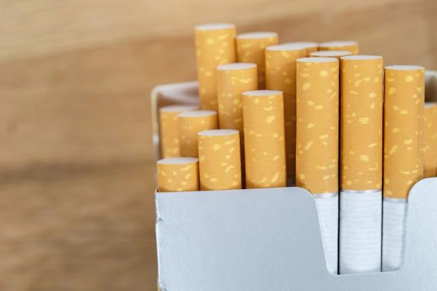 Afbeelding van verschillende commercieel gemaakte sigaretten. stapel stapel sigaret op houten. of niet-roken campagneconcept, tabak