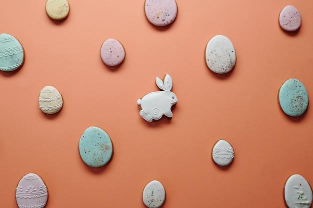 Afbeelding van versierde zelfgemaakte peperkoek taarten in de vorm van konijn en eieren geïsoleerd op oranje achtergrond