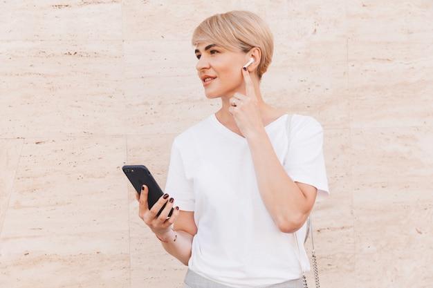 Afbeelding van volwassen blonde vrouw, gekleed in wit t-shirt met behulp van mobiele telefoon, terwijl staande tegen beige muur buiten en draadloze oortelefoon aan te raken
