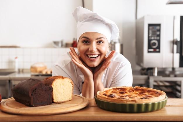 Afbeelding van volwassen vrouw chef-kok dragen witte uniform, poseren in de keuken in het café met gebakken goederen