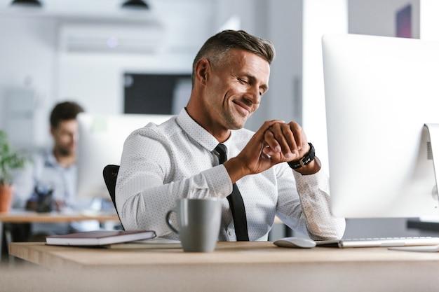Afbeelding van volwassen zakenman 30s dragen witte overhemd en stropdas zitten aan de balie in kantoor door computer, en kijken naar polshorloge