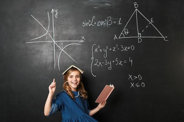 Afbeelding van vrij gelukkig jong schoolmeisje poseren geïsoleerd over schoolbord muur muur.