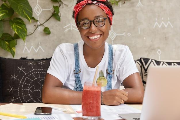 Afbeelding van vrij vrolijke zwarte vrouw heeft online conferentie met collega's, tevreden met testresultaten