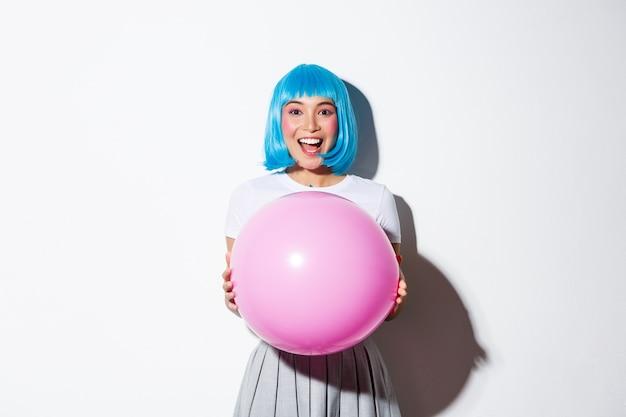 Afbeelding van vrolijk aziatisch meisje in blauwe pruik, vakantie vieren, outfit dragen voor halloween-feest