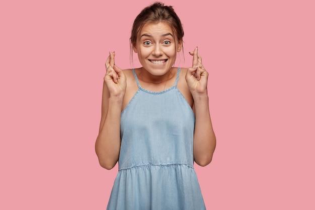Afbeelding van vrolijk meisje heeft grappige blije uitdrukking, maakt wenselijk gebaar, vingers gekruist
