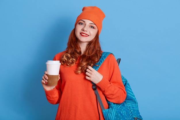 Afbeelding van vrolijke blanke vrouw in hoed koffie drinken terwijl rugzak
