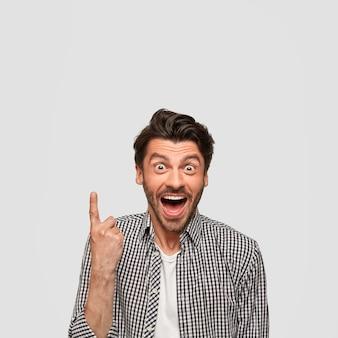 Afbeelding van vrolijke gelukkige jonge blanke man met verbaasde uitdrukking, wijst naar boven, staart met afgeluisterde ogen