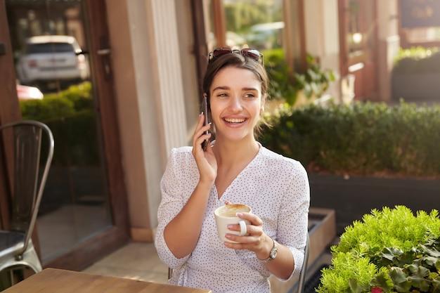 Afbeelding van vrolijke jonge brunette vrouw met kopje koffie in opgeheven hand telefoongesprek hebben en vreugdevol glimlachen, zittend aan tafel over stad café interieur