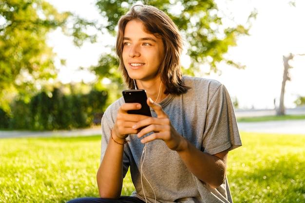 Afbeelding van vrolijke jonge kerel luisteren muziek met koptelefoon in het park chatten via de telefoon.