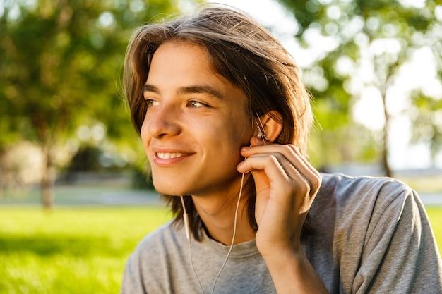 Afbeelding van vrolijke jonge kerel luisteren muziek met koptelefoon in het park.