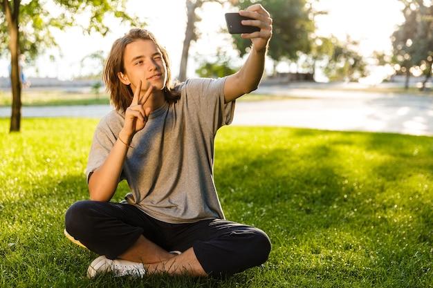 Afbeelding van vrolijke jonge kerel zittend op het gras in het park met behulp van telefoon, neem een selfie.