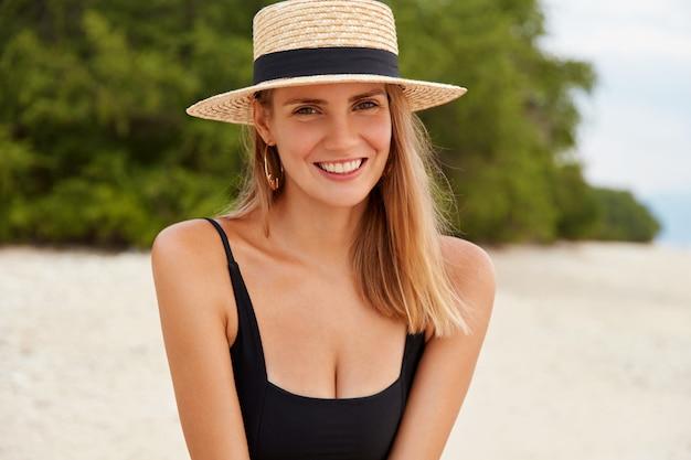 Afbeelding van vrolijke jonge mooie vrouw rust aan de oceaankust, in een goed humeur, net als een lange zomervakantie en een onvergetelijk resort in een tropisch land.
