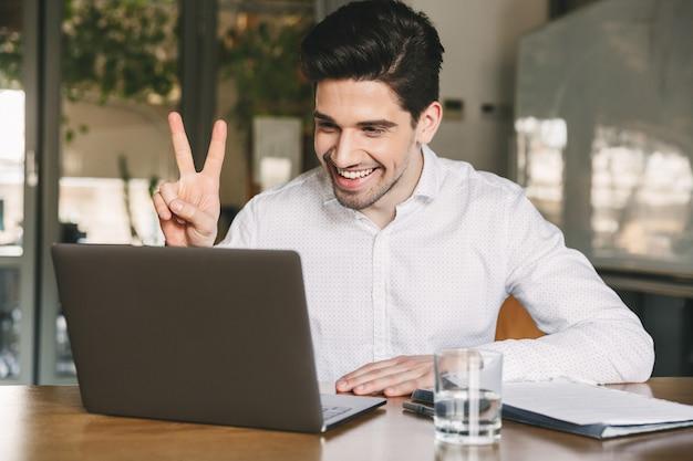 Afbeelding van vrolijke office man 30s dragen wit overhemd lachen en vredesteken tonen op laptop, tijdens videoconferentie of oproep
