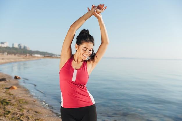 Afbeelding van vrolijke sport vrouw warming-up en naar beneden te kijken