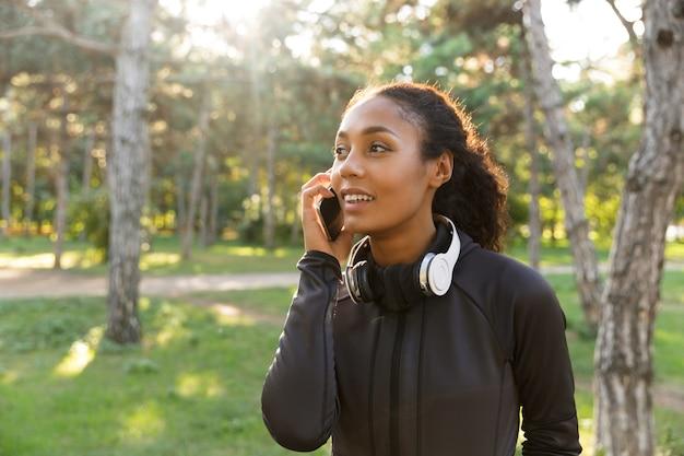 Afbeelding van vrolijke vrouw 20s dragen zwarte trainingspak en koptelefoon, met behulp van mobiele telefoon tijdens het wandelen door groen park