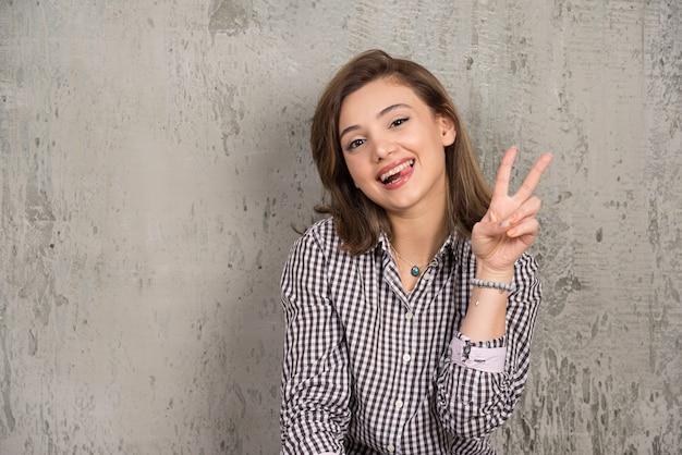 Afbeelding van vrolijke vrouw die vrijetijdskleding draagt die en vredesteken met twee vingers glimlacht toont