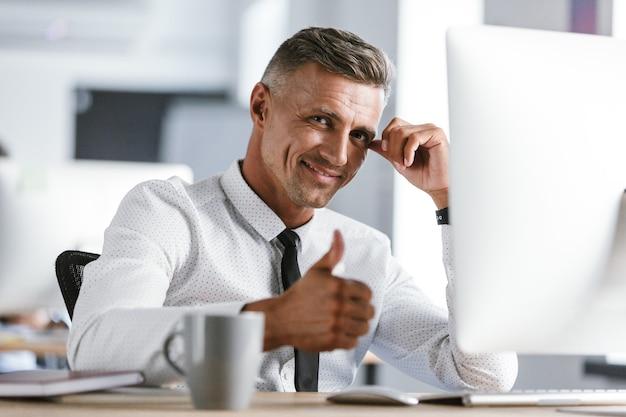 Afbeelding van vrolijke zakenman 30s dragen witte overhemd en stropdas zit aan bureau in kantoor door computer, en duim opdagen