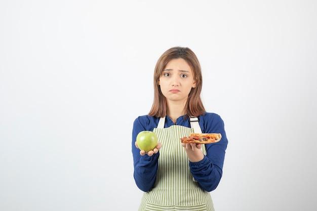 Afbeelding van vrouw in schort die probeert te kiezen wat ze appel of pizza gaat eten