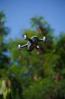 Afbeelding van witte en grijze drone die vliegt, met bomen en lucht eromheen.