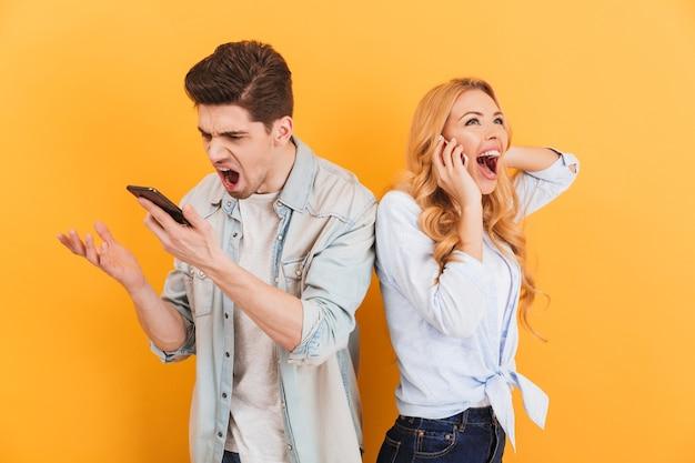 Afbeelding van woedende man schreeuwen in smartphone terwijl gelukkige vrouw met aangenaam mobiel gesprek