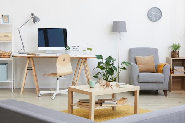 Afbeelding van woonkamer met werkplek met computermonitor erop en ander modern meubilair in huis