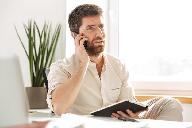 Afbeelding van zakelijke man 30s dragen wit overhemd met behulp van smartphone en laptop, zittend aan tafel op de moderne werkplek