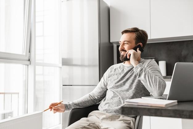 Afbeelding van zakelijke man jaren '30 die casual kleding dragen die op laptop werkt, terwijl hij uit het raam kijkt en thuis op mobiele telefoon spreekt