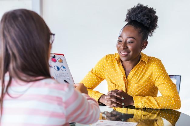 Afbeelding van zakelijke partners discussiëren over documenten en ideeën op vergadering