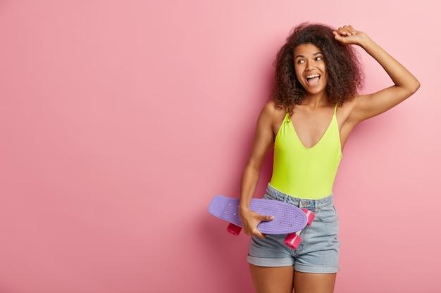 Afbeelding van zorgeloze optimistische afro vrouw met donkere huid, dansen actief met skateboard, heeft plezier in zonnige dag