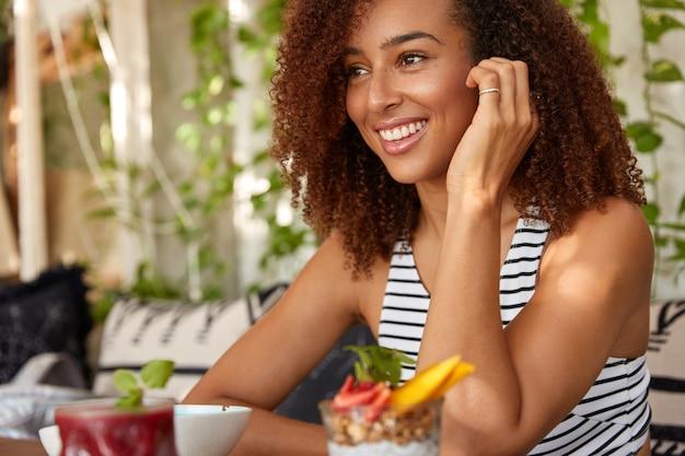 Afbeelding van zwarte vrouw zit zijwaarts met blije uitdrukking