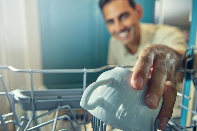 Afbeelding vanuit een vaatwasser van een jonge man die onscherp lacht en een witte mok oppakt met zijn hand op de voorgrond