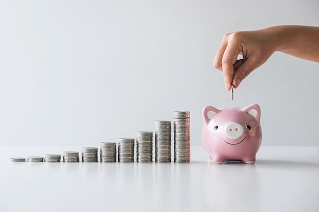 Afbeeldingen van stapelmunten stapelen en hand munt in roze spaarvarken stoppen om te groeien en te sparen met spaarpot, geld besparen voor toekomstig plan en pensioenfonds