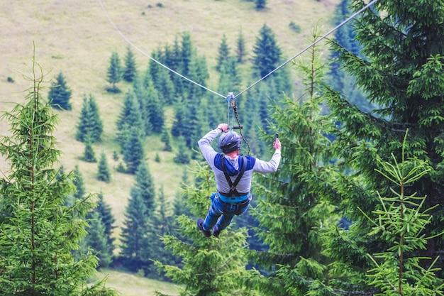 Afdaling van de berg op een metalen kabel zipline is een extreem soort plezier in de natuur