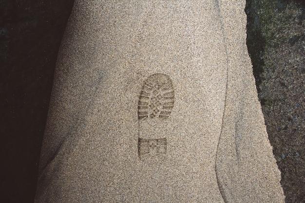 Afdruk van de schoen op modder met kopieerruimte voetstap op zand achtergrondtextuur